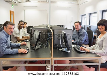Happy  group in a computer room in college