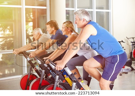 Happy group in gym exercising on bikes in summer - stock photo