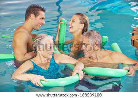 Happy group in swimming pool doing aqua fitness with swim noodles - stock photo