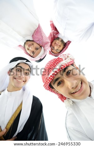 Happy group of Arabic people with heads together in circle over sky background - stock photo