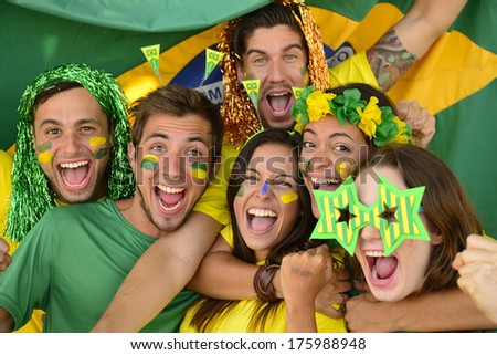 Happy group of Brazilian sport soccer fans amazed celebrating victory together. - stock photo