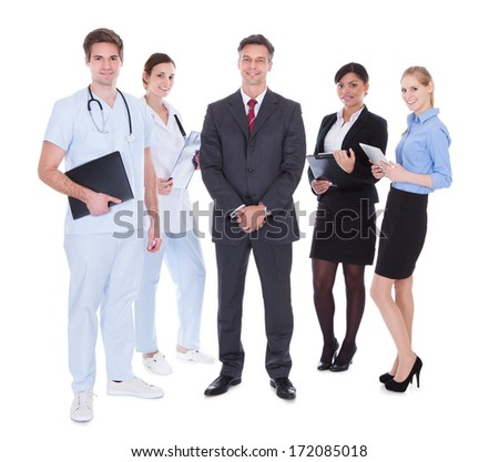 Happy Group Of Businesspeople And Doctors Standing Over White Background