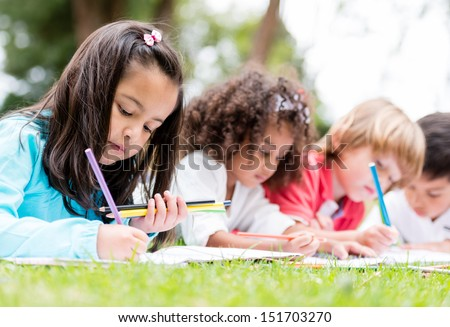 Happy group of children coloring at the park  - stock photo