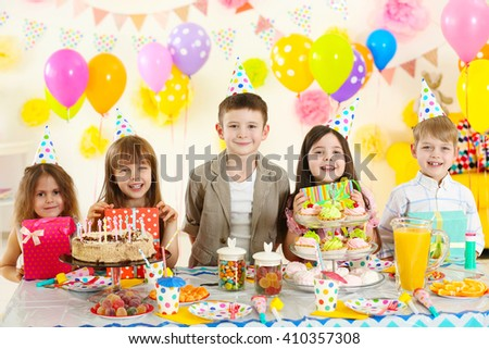 Happy group of children with gift boxes at birthday party