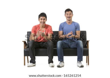 Happy group of Chinese friends sitting on a sofa watching sport & celebrating. Isolated over white background
