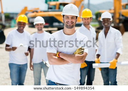 Happy group of construction workers at a building site  - stock photo