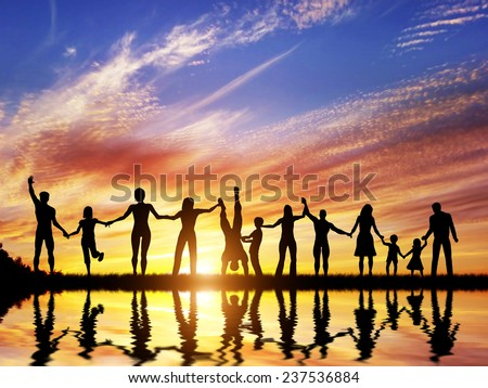 Happy group of diverse people, friends, family, team standing together holding hands and celebrating success. Water reflection, sunset sky - stock photo