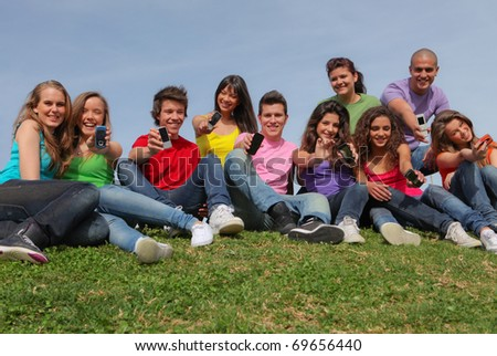 HAPPY GROUP OF DIVERSE TEENAGERS SHOWING MOBILE TELEPHONES OR CELL PHONES