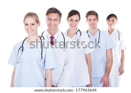 Happy Group Of Doctors And Nurses Standing In A Row Over White Background