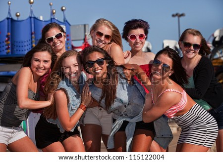 Happy group of eight teenage girls together at a theme park
