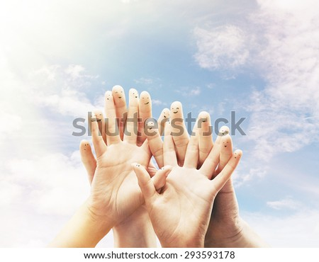 Happy group of finger smileys on sky background - stock photo