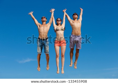 Happy group of friends at the beach - stock photo