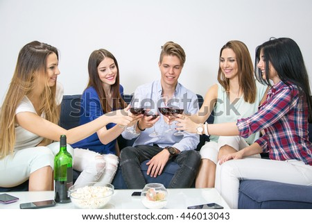 Happy group of friends clinking glasses of wine at home.