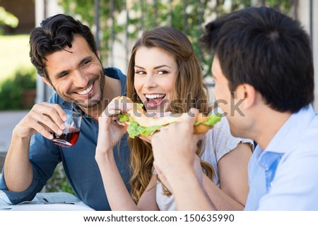 Happy Group Of Friends Eating Sandwich With Fun Outdoor - stock photo