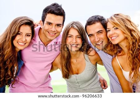 Happy group of friends hugging and smiling outdoors