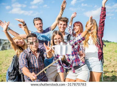 Happy group of friends photographing themselves with selfie stick - Hikers on excursion in the nature having fun and gesturing in front of the camera