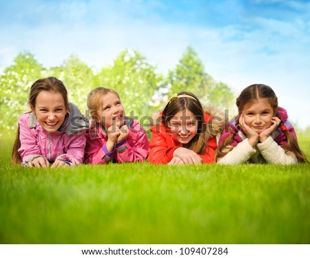 Happy group of girls lying on a green grass