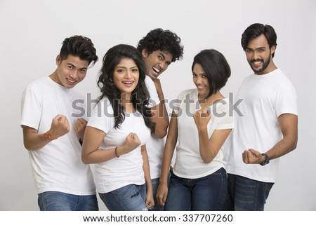 Happy group of Indian students showing success sign on white background.