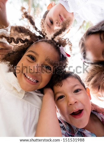 Happy group of kids hugging at the park - stock photo