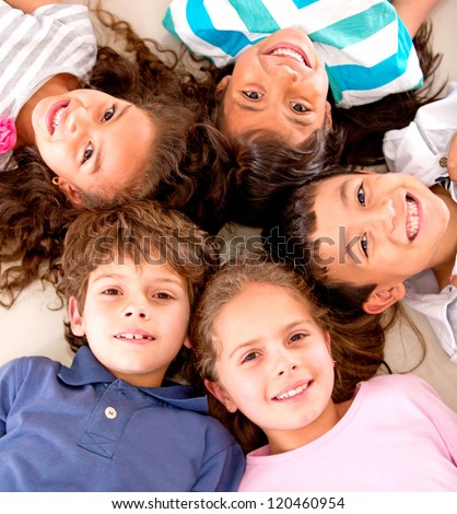 Happy group of kids lying on the floor with heads together - stock photo
