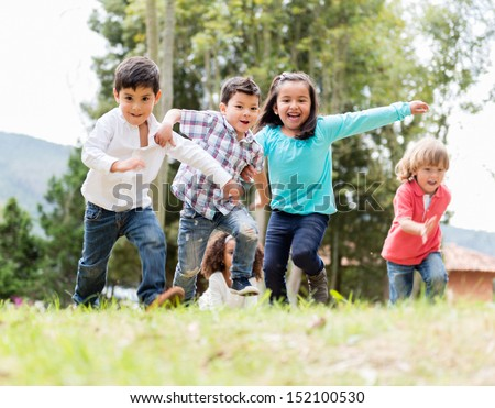 Happy group of kids playing at the park  - stock photo