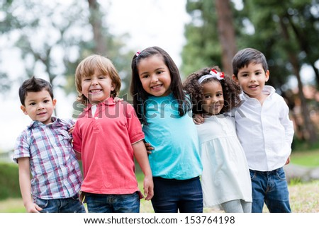 Happy group of kids smiling at the park  - stock photo