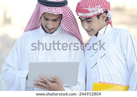 Happy group of Middle eastern Gulf boys using laptop