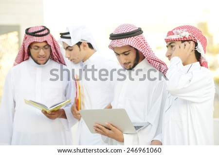 Happy group of Middle eastern Gulf boys using laptop - stock photo
