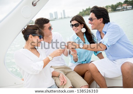 Happy group of people on a boat making a toast - stock photo