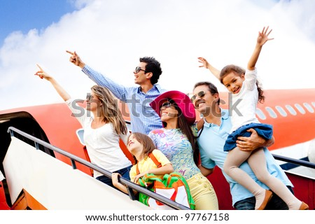 Happy group of people traveling by airplane on their holidays - stock photo