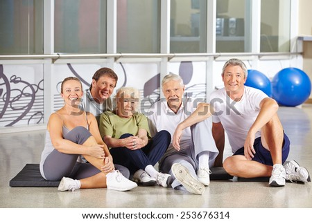 Happy group of senior people sitting in gym and smiling - stock photo