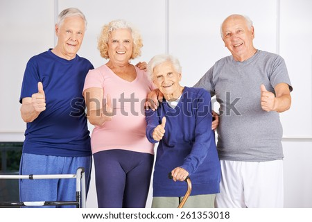 Happy group of seniors holding thumbs up in a nursing home - stock photo