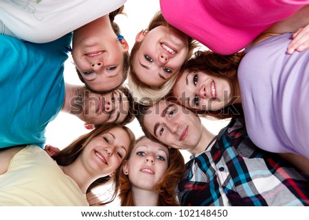 happy group of smiling friends holding heads together in circle - stock photo