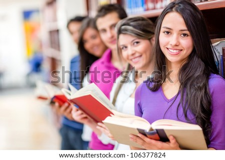 Happy group of students at the library holding books - stock photo