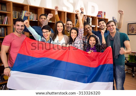 Happy group of students from Serbia with raised victory fists, presents their country with flag  - stock photo