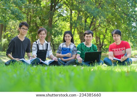 Happy group of students sitting at the park - stock photo
