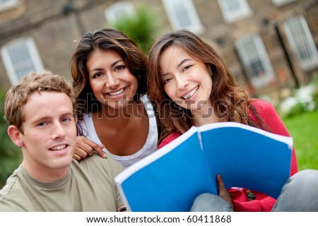 Happy group of students with a notebook outdoors - stock photo