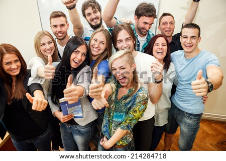 Happy group of students with thumbs up - stock photo
