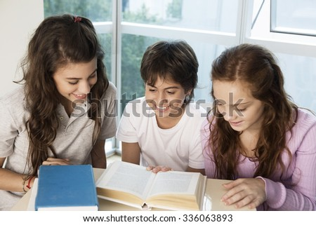 Happy group of teen students reading