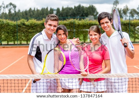 Happy group of tennis players at the court smiling