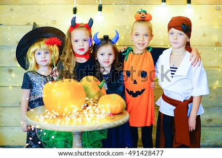 Happy group of witch children, pirate and demons during Halloween party playing around the table with pumpkins