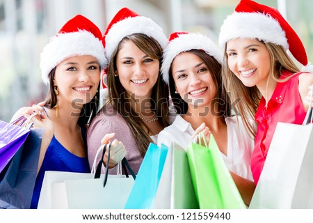 Happy group of women Christmas shopping at the mall - stock photo