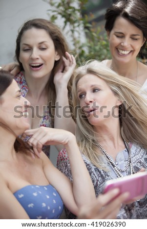 Happy group of women talking and having fun with mobile phone