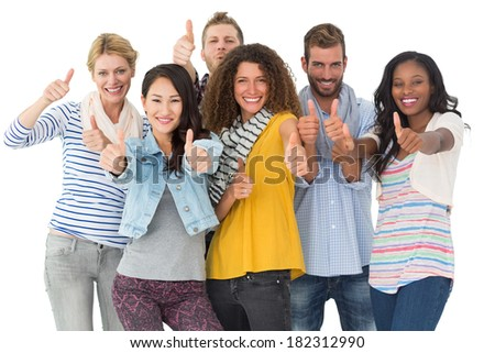 Happy group of young friends giving thumbs up to camera on white background - stock photo