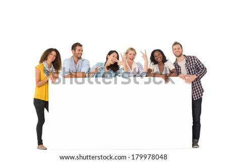 Happy group of young friends leaning on large poster on white background - stock photo