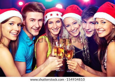 Happy group of young friends touching the glases with each other - stock photo