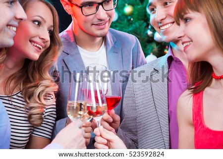 Happy group of young friends touching the glases with each other