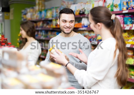 Happy group of young people to choose canned in grocery store