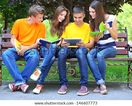 Happy group of young students sitting in park