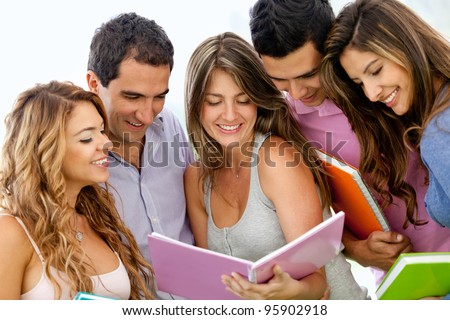 Happy group of young students with a notebook outdoors